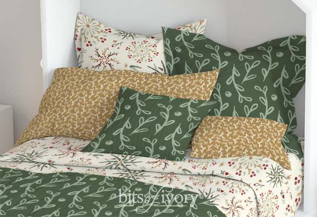 bed with pillows showing different patterns of cloth from the warm winter woods collection