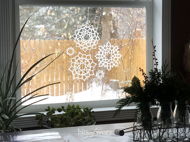 A winter view from a window with paper snowflakes on it.